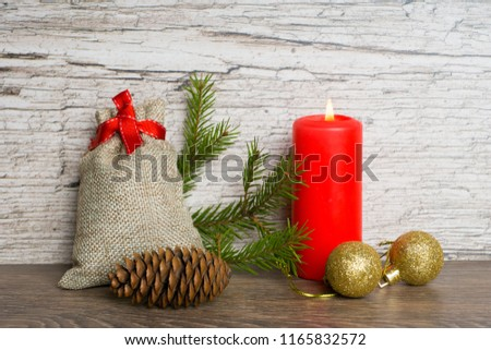 red candle with christmas fir tree decorations and gift bag #1165832572