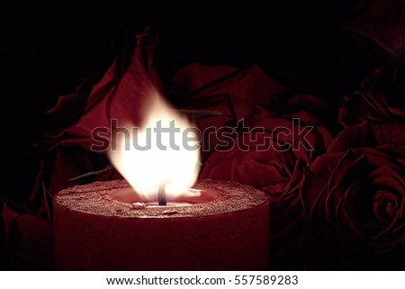 Red Candle with Red Rose Background and Flame Blowing - Photograph of a red burning candle with red roses as a background and filter on image for effect. Great for Valentine's Day! #557589283