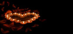 Red candles are arranged in the shape of a heart on a dark background. There are rose petals all around. Banner with space for text.