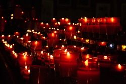 Red candles in church forming converging lines