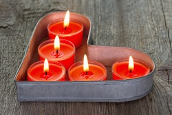 Red candles on a heart shaped tray on a rustic wooden background