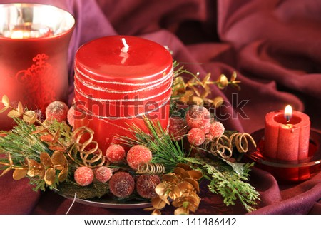 Red Candles Red holiday candles surrounded by holiday decorations. The Background of the image is burgundy suede.