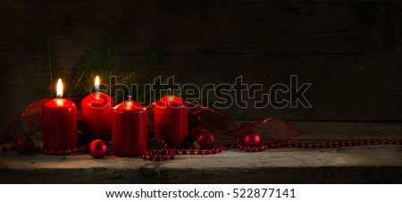 Red candles, two of them burning on the second advent, christmas decoration with baubles on a rustic board, dark wooden background with copy space, panorama banner or website header, selective focus