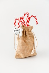 Red candy canes in jute sack with jingle bells and Christmas star isolated on white. Low angle view.