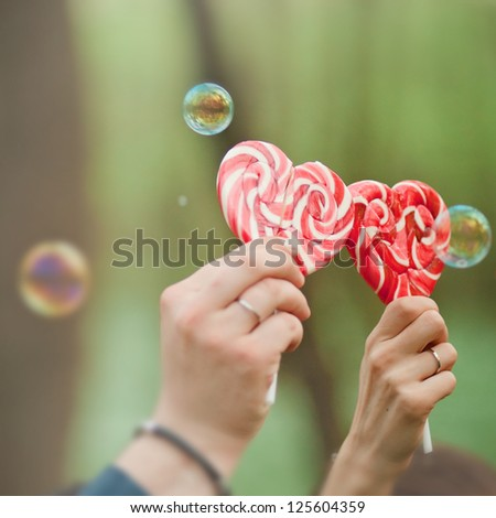Red candy heart in woman and man hands, on green background