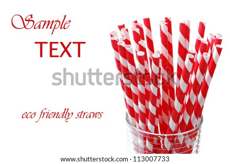 Red 'candy striped' environmentally friendly straws (biodegradable paper printed with soy-based ink) on white background with copy space.  Macro with shallow dof.