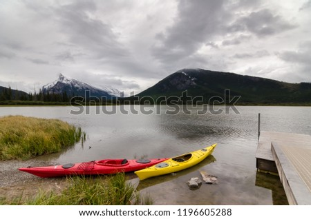 Red canoe and yellow canoe sitting by a dock with a view of Mount Rundle on Vermillion Lakes in Banff National Park, Alberta, Canada