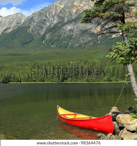 Red canoe moored on the bank of the mountain lake. Jasper National Park, Alberta, Canada