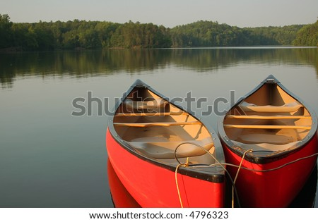 Red canoes on a calm evening at the lake - stock photo