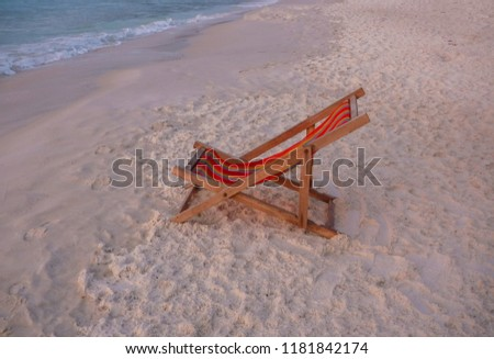 Red canvas bed is located on  beach alone. In sea without people - Shutterstock ID 1181842174