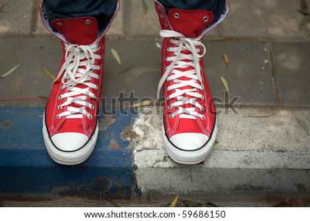 Red canvas sneakers on sidewalk