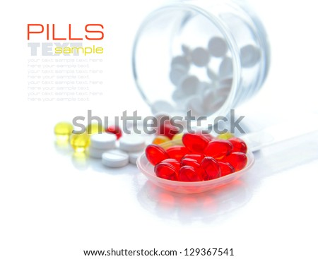 Red capsules are in a spoon on a background the color capsules