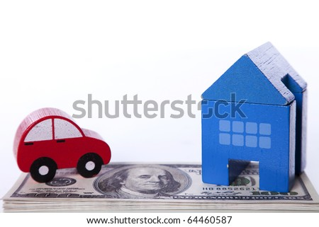 red car and blue house over a lot of dollar bills isolated on white  (selective focus)