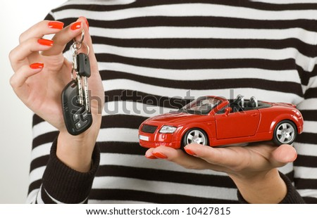 Red car and keys in the woman's hands