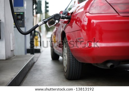 Red car at gas station being filled with fuel. Shallow DOF. - stock photo