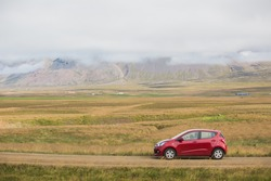 Red car at the beautiful foggy landscape of iceland
