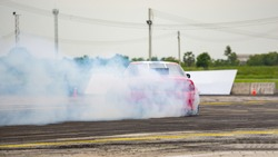 Red Car drifting, Car wheel spinning with smoke coming from wheels, Drag Racing on asphalt track.