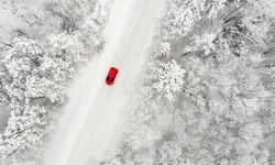 red car driving on a snow covered iced road in winter time