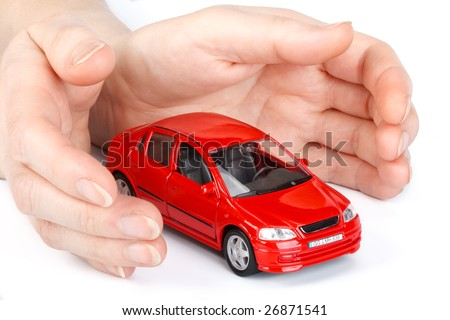 Red car in hands on a white background. Concept of safe driving - stock photo
