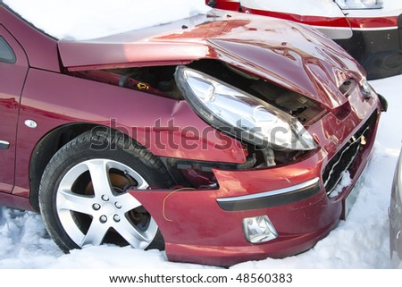 Red car in winter crushed. Damage front of vehicle.