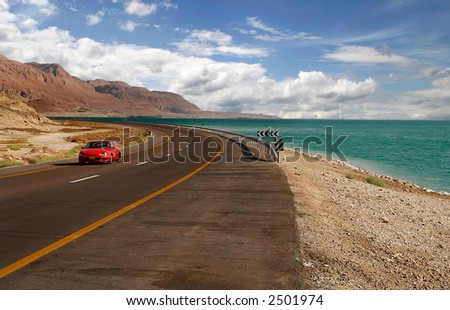 Red car on a highway that runs along the Dead Sea from one side and Edom Mountains at Arava Desert from the other in Israel.