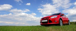 red car on green grass against sky