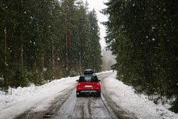 Red car with roof rack driving on a forest road in winter, heavy snowfall. The concept of traveling by car