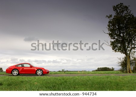 Red Car with Storm Clouds