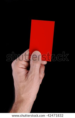 Red card in hands. Soccer referee is holding red card, isolated on black background.