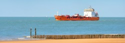 Red cargo tanker ship sailing next to the coast of Vlissingen, the Netherlands. Freight transportation, nautical vessel, fuel and power generation, logistics, industry, environment. Panoramic view