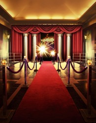 Red carpet entrance with barriers, velvet ropes and lights in the background