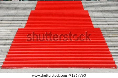 Red carpet on marble stairway welcoming VIPs.