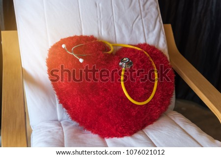 Red cartoon heart pillow put on white arm chair with yellow stethoscope. #1076021012