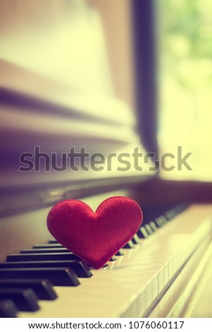 Red cartoon heart put on keyboard's piano, To tell love to learn music or to tell someone love in special day and valentine day. #1076060117