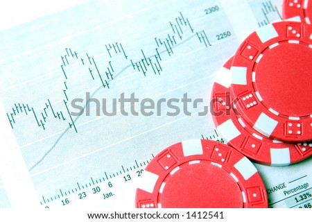 Red casino chips on top of a financial newspaper.
