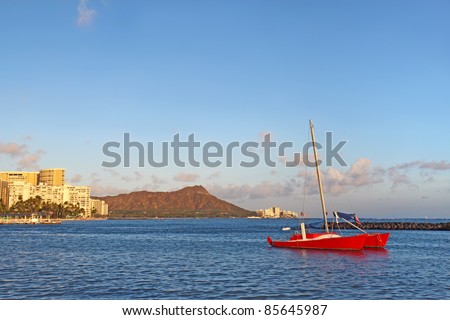 Red catamaran and several hotels along Waikiki beach at Honolulu, Hawaii, with the volcanic cone of Diamond Head in the background
