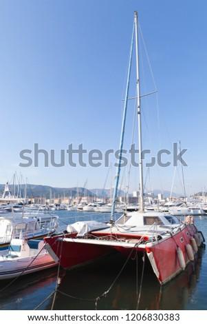 Red catamaran yacht  moored in marina of Ajaccio. Corsica, French island in the Mediterranean Sea #1206830383