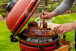 Red Ceramic Barbecue Grill. The man coats pork ribs with BBQ sauce. Grilling, Smoking, Baking, BBQ and Roasting process. Post-quarantine Picnic in modern homes terrace. Lifestyle concept.