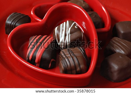 Red ceramic heart dishes with assorted chocolate candies.  Macro with shallow dof. - stock photo