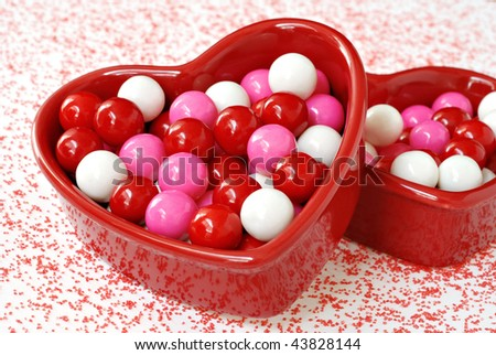 Red ceramic heart-shaped dishes with colorful valentine gumballs and red sugar sprinkled around.  Macro with shallow dof.