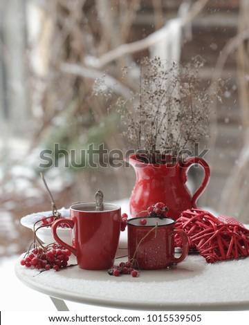 Red ceramic mugs wit h tea in the snowy garden