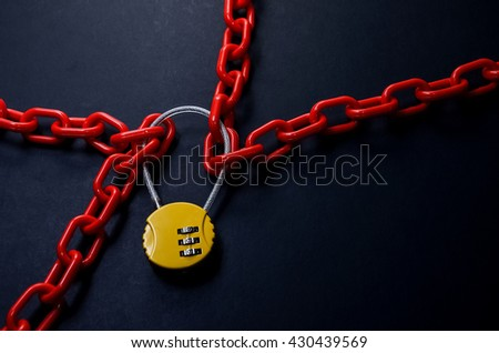 Red chain and yellow padlock with number combination on blackboard.