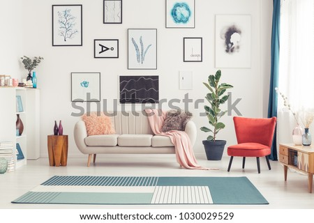 Red chair and blue carpet near couch in colorful living room interior with ficus and posters #1030029529