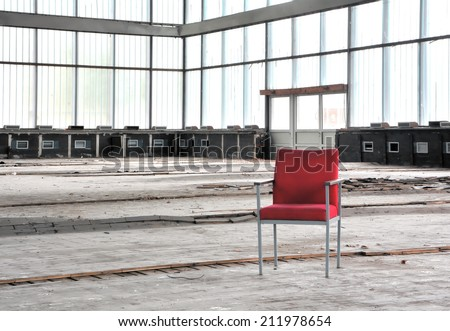 Red chair in an abandoned dilapidated event room
