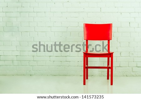 Red chair in empty room against a brick wall with copy-space