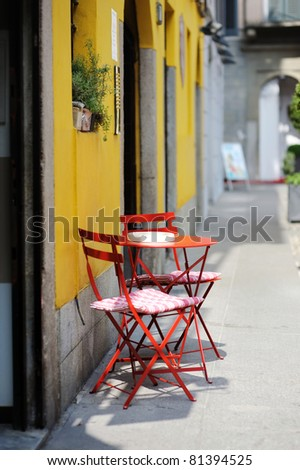 Red chairs against a yellow painted wall in Italy