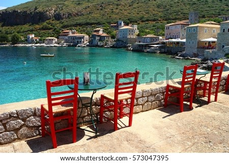 Red chairs and tables of a traditional cafe in Mani, Peloponnese, overlooking the blue sea and the stone houses