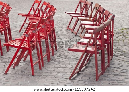 red chairs in open air on cobbles