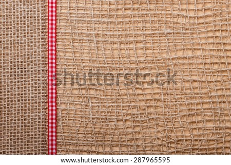 Red checked ribbon on brown mesh jute material, natural burlap ecology background