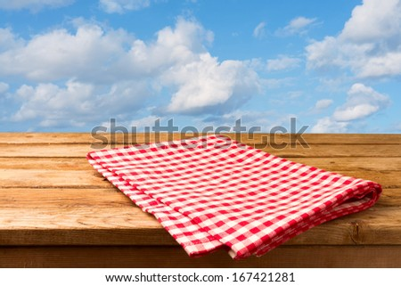 Red checked tablecloth and empty deck wooden table over blue sky